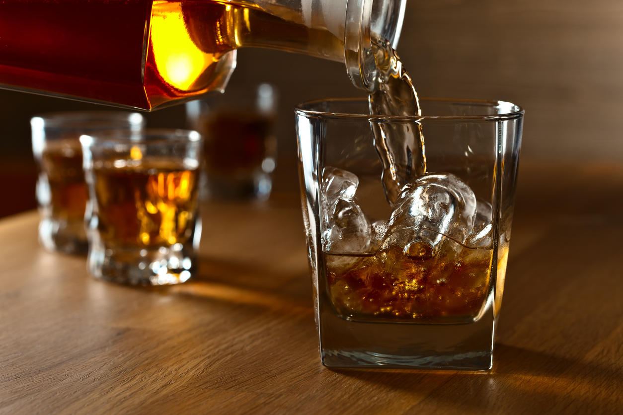 Whiskey with natural ice on a oak table.